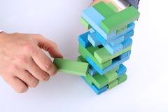 Planera, risk och strategi i affären, affärsman som ut får ett träkvarter från ett torn Arkivbild