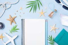 Planera sommarferier, tur och semesterbakgrund Handelsresandeanteckningsbok med tillbeh?r p? bl? b?sta sikt f?r tabell Lekmanna-  arkivbild