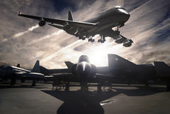 Planes. A Boeing 747 flying over landed planes Stock Photo