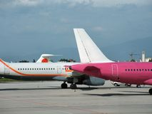 Planes in airport. Two airplanes in an airport, a pink and a white one Royalty Free Stock Photos