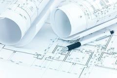 Planes arquitectónicos, rollos del modelo y lápiz en el DES del arquitecto fotografía de archivo