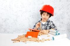 Planes del muchacho para construir una casa Fotos de archivo