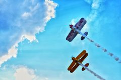 Planes. Orange blue sky fly flight togheter tandem team clouds smoke diagonal stock photos