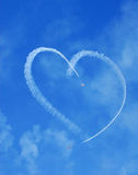 Planes Skywriting Heart. Vintage aircraft with smoke display creating heart shape in sky Royalty Free Stock Photo