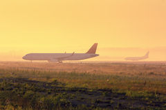 Planes on the taxiway. In the early foggy morning Stock Photography
