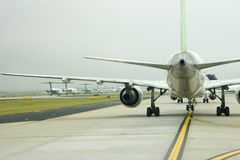 Planes Under Wing. View of airplanes lined up for takeoff under another airplane's wing royalty free stock photography
