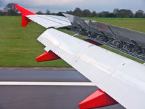 Planes wing flaps open. Shot of a planes wing with the flaps fully open showing the internal mechanics as it comes into land Stock Images