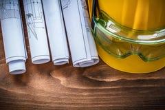 Planes y casco de la construcción de las gafas en tablero de madera marrón Foto de archivo