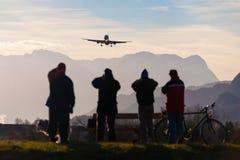 Planespotters que toma a foto de uma aterrissagem de avião no aeroporto de Salzburg durante a estação do voo charter do inverno c imagens de stock