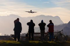 Planespotters taking photo of an airplane landing at Salzburg airport during winter charter flight season with Alps stock images