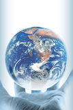 Planet conservation. A hand with planet earth hovering above and copy-space for your text Royalty Free Stock Image