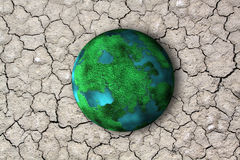 Planet and dry soil with crack. Climate change concept with earth planet on dry soil and copyspace Royalty Free Stock Image