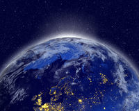 Planet earth with appearing sunlight. Visible city lights. Royalty Free Stock Photos