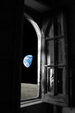 Planet Earth away from old window   loneliness. Conceptual picture of Earth away out of Royalty Free Stock Photos