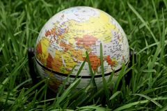Planet earth balloon over grass Royalty Free Stock Images