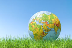 Planet earth balloon over grass. Inflated topographical planet earth balloon over grass royalty free stock photography