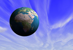 Planet Earth in blue sky. Close up of plant Earth with continent of Africa prominent, blue sky and cloudscape background Royalty Free Stock Image