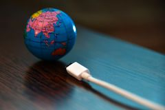 The planet earth is charging from the network, through a white cable. The planet earth is charging from the network, through a white cable stock image