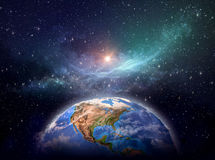 Planet Earth in cosmic space. Planet Earth focused on North America, star cluster and nebula in outer space, bright light shining far behind - Elements of this Stock Images