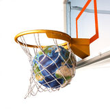 Planet Earth falling into the basketball basket by a perfect shot. Royalty Free Stock Image