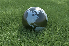 Planet Earth on Grass Field. Clouds and earth map comes from http://earthobservatory.nasa.gov Royalty Free Stock Photography