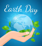 Planet Earth and green leaves in hand. On a blue background. Card for Earth Day Royalty Free Stock Photos