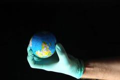 Planet Earth and a Hand. Planet Earth and Hand on a Black Background stock photos