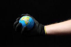 Planet Earth and a Hand. On Black Background stock photography