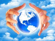Planet earth in the hands. Hands and lighting earth planet in the sky with clouds Royalty Free Stock Image