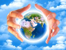 Planet earth in the hands. Hands and lighting earth planet in the sky with clouds Royalty Free Stock Photos