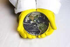 Planet earth in hands with yellow lab gloves. Hands with yellow rubber gloves cradling planet earth with white lab coat.  Blue Marble image compliments of NASA Royalty Free Stock Images