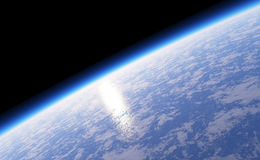 Planet earth from the space. The planet earth, full of clouds and a large ocean, with the atmosphere and the reflection of the sun Royalty Free Stock Photo