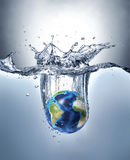 Planet Earth, splashing into water. Planet Earth, splashing into water, forming a beautiful dramatic splash with gradient background and lighter under water Royalty Free Stock Images