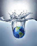 Planet Earth, splashing into water. Planet Earth, splashing into water, forming a beautiful dramatic splash with gradient background and lighter under water Royalty Free Stock Photo