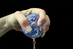 Planet earth squeezed and squashed. Dripping on black background Stock Photo