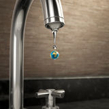 Planet earth water drop coming out of the tap Stock Photo