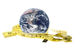 Planet Earth Yellow Measuring Tape Isolated. Isolated macro image of planet earth with a measuring tape Stock Photo