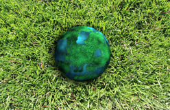Planet and green grass. Climate change concept with earth planet on green grass Royalty Free Stock Photography