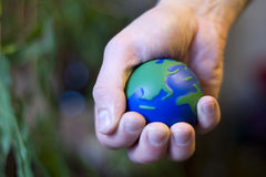 Planet hand. Ecological vision where human hand squeeze our planet Royalty Free Stock Image