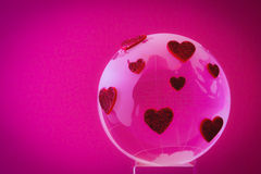 The planet of love. Glass globe with red hearts. Stock Photo