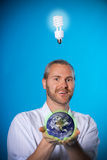 Planet-minded. Man with a beard with a light bulb holding a planet royalty free stock photo