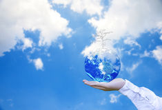 Planet and tree in human hands over blue sky with white clouds, Save the earth concept, Royalty Free Stock Photo
