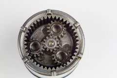 Planetary gear from a small device on a bright table. Gear wheel. S from a specialist device. White background stock image