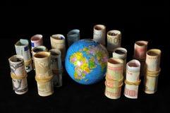 Planeten-Erde und gerolltes Geld Lizenzfreie Stockfotos