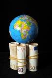 Planeten-Erde und gerolltes Geld stockbild