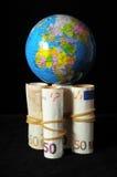 Planeten-Erde und gerolltes Geld Stockfotos
