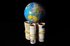Planeten-Erde und gerolltes Geld Lizenzfreie Stockbilder