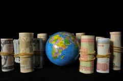 Planeten-Erde und gerolltes Geld Lizenzfreies Stockfoto