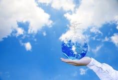 Planeten och trädet i människahänder över blå himmel med vitmoln, sparar jordbegreppet, royaltyfri foto