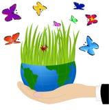 Planetenerde auf einer Hand und einem hellen Schmetterling Lizenzfreie Stockfotografie